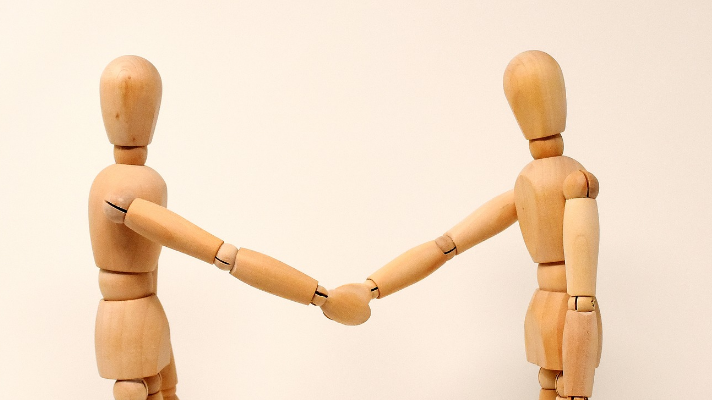 wooden models shaking hands courtesy of spark post