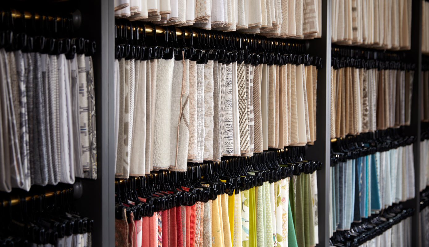 a wall of various fabric samples on hangers