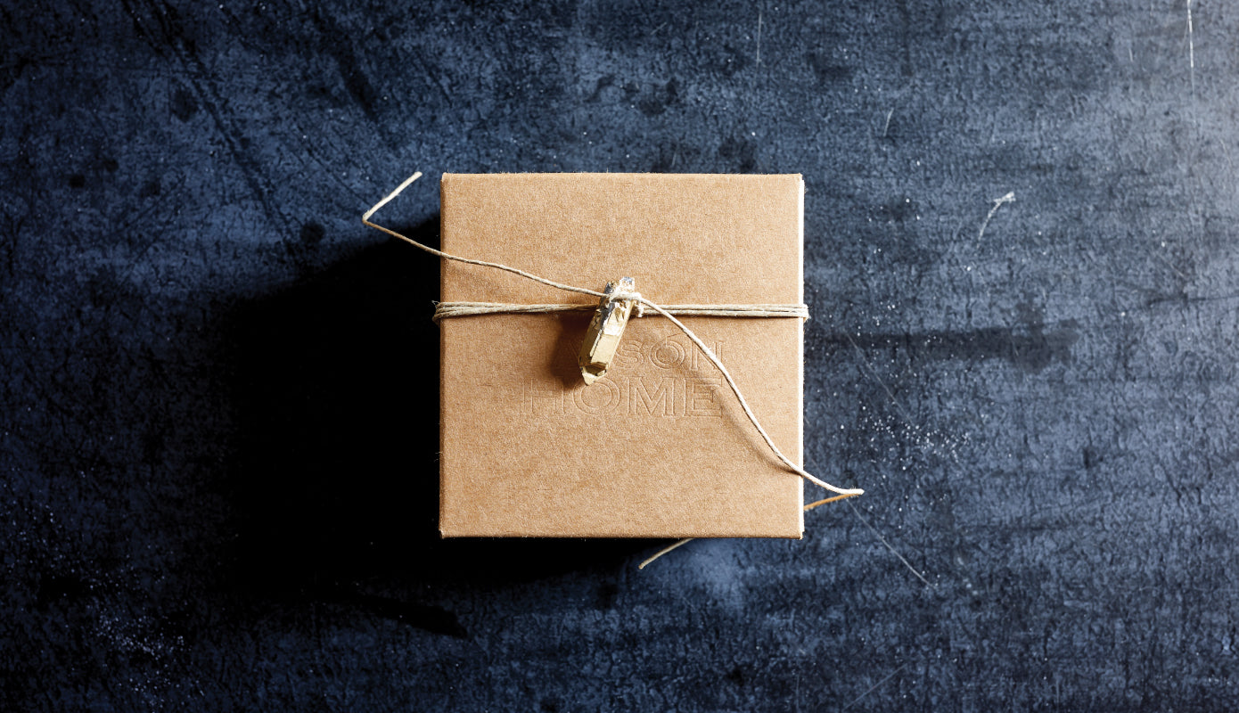Cardboard Gift Box hand tied with twine and a quartz charm on blue background