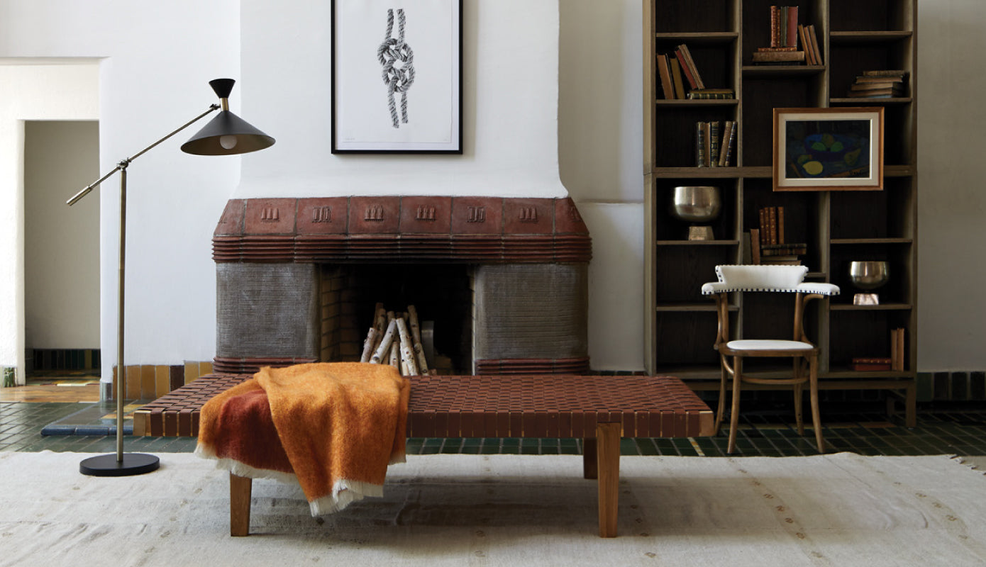 Beacon woven leather Daybed, orange mohair throw, Newell armchair in front of fireplace