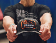 "Load image into Gallery viewer, NEW ""We The Essentials"" Multicam Black Trucker Hat with Orange Patch"