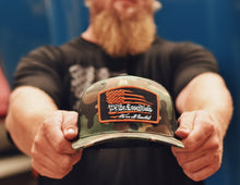 "Load image into Gallery viewer, NEW ""We The Essentials""  - Camo Trucker Hat with Orange Patch"