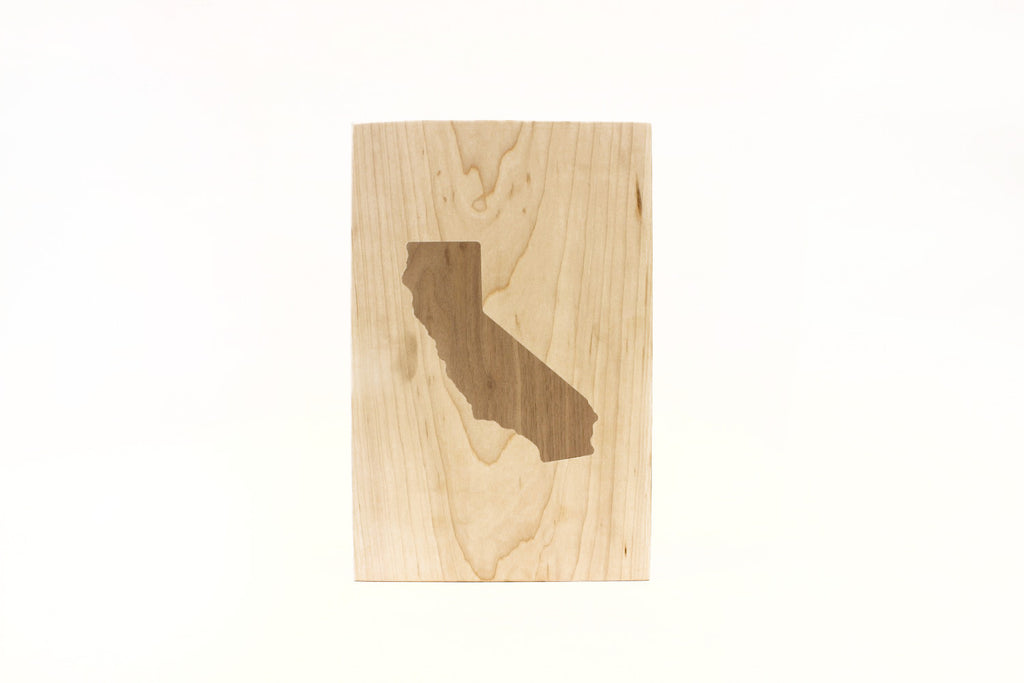 A display board made from reclaimed maple and walnut wood with a solid inlay of the state of California.