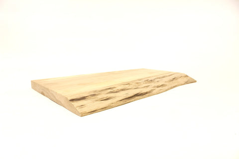 A cutting board made from reclaimed oak with a natural wood edge.