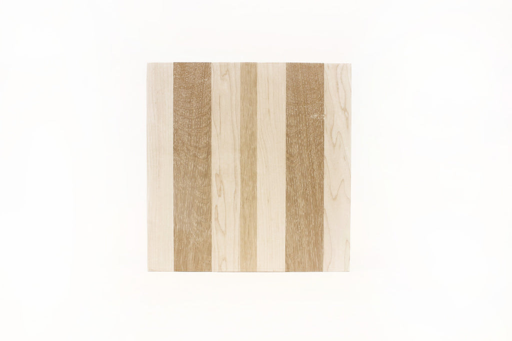 A thick, striped cutting board made from reclaimed oak and walnut.