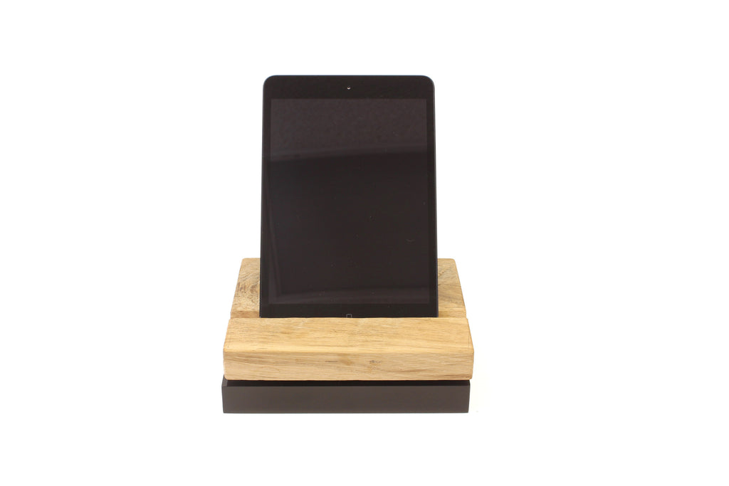 A rotating stand for iPhones and iPads made from black polished acrylic and reclaimed wood.