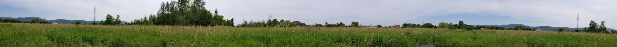 Panoramic view of a field with the Gatineau hills in the background