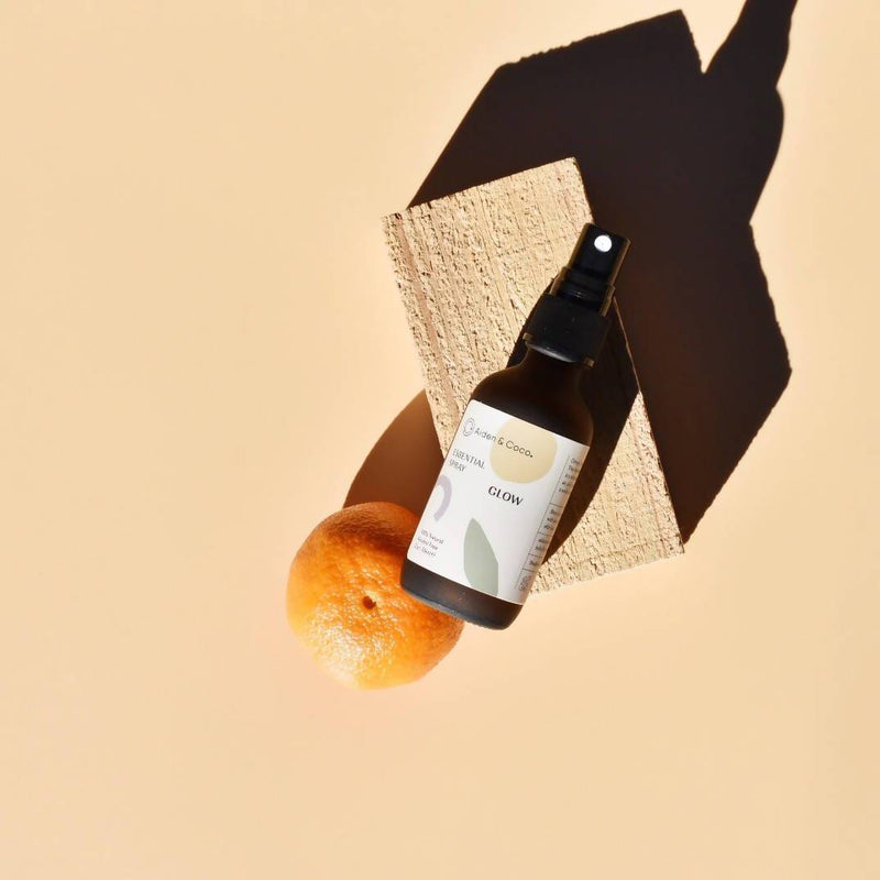 bottle of aiden & coco glow essential spray on brick next to orange