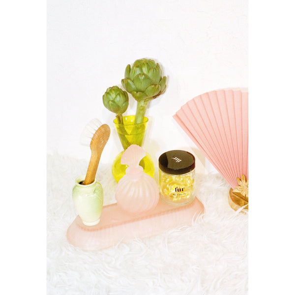 jar of fur bath drops surrounded by artichokes brush perfume fan