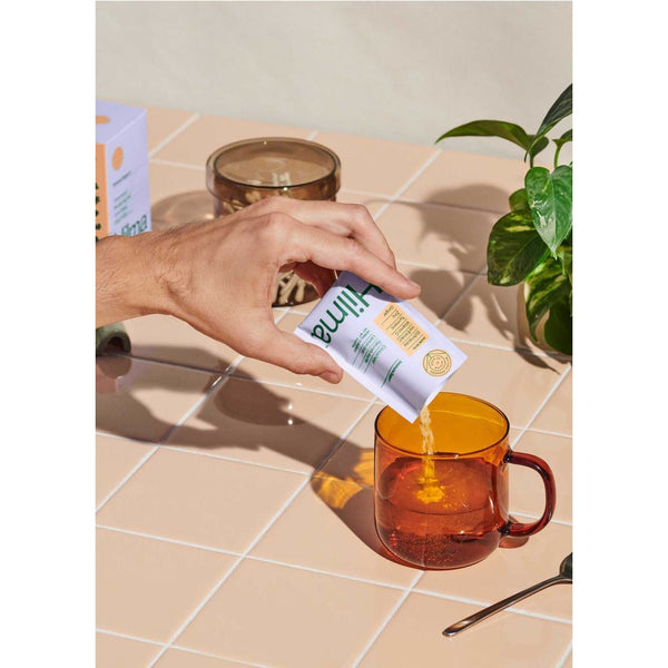 hand pouring hilma immune support herbal supplement in water
