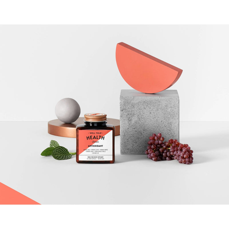 bottle of well told health antioxidant whole food dietary supplement next to geometric blocks and grapes