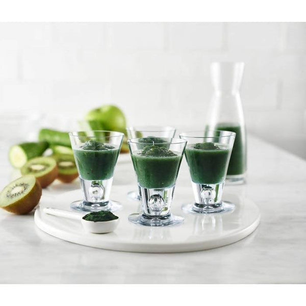 glass cups of yourlixir organic spirulina beauty + wellness powder drink on marble counter top next to kiwis
