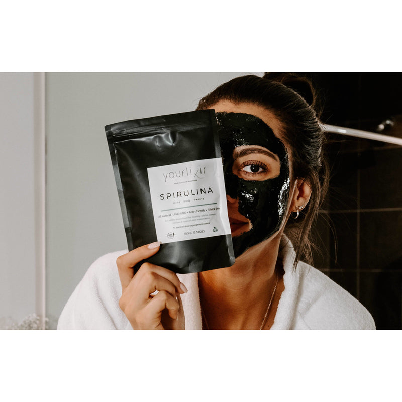 woman with black face mask holding bag of yourlixir organic spirulina beauty + wellness powder