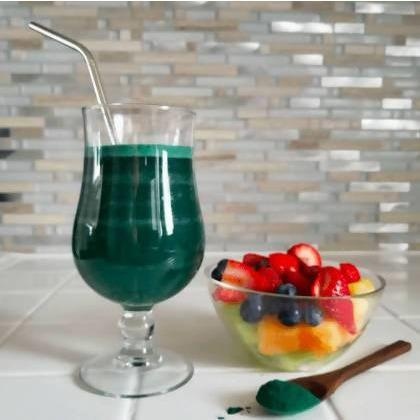 glass of yourlixir organic spirulina beauty + wellness powder drink next to bowl of fruits and spoon of powder