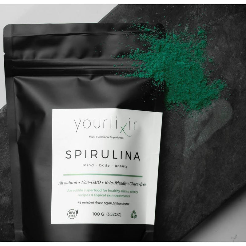 bag of yourlixir organic spirulina beauty + wellness powder with some powder on top