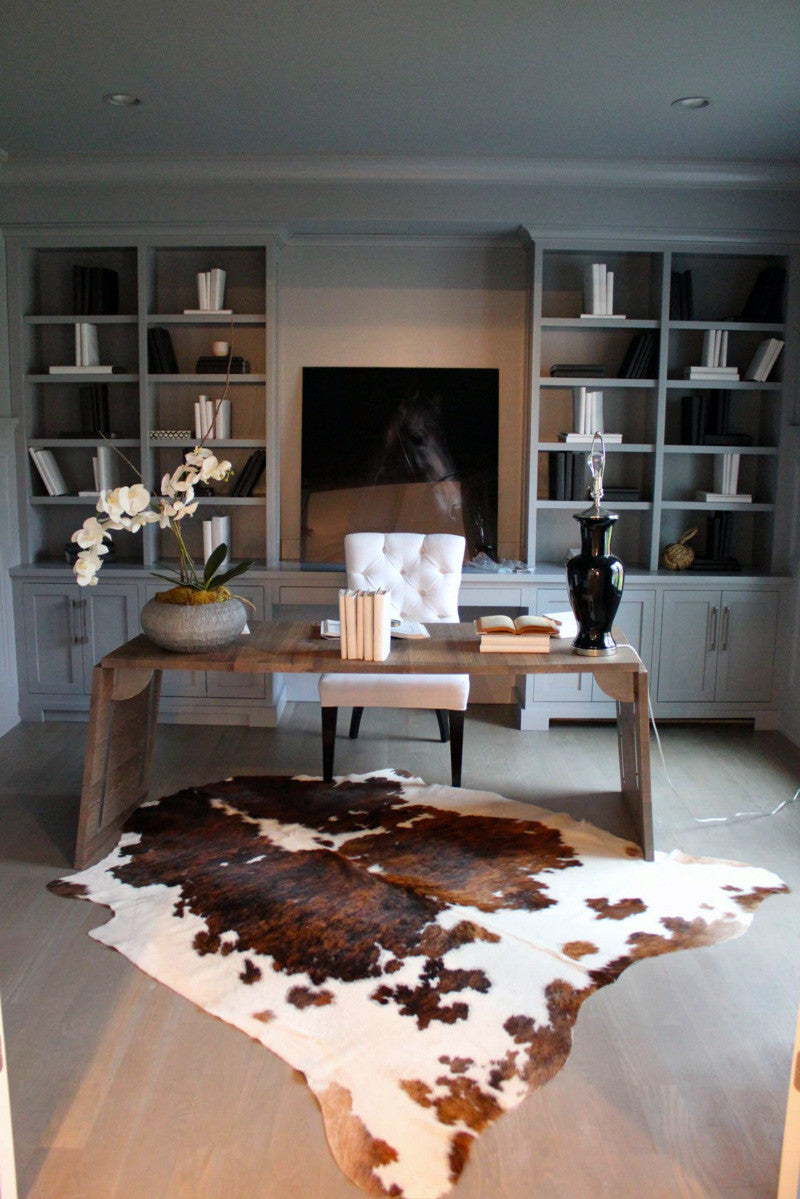 Large tri color spotted cowhide rug in room