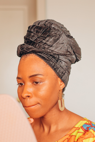 Black woman working from home wearing a black headwrap