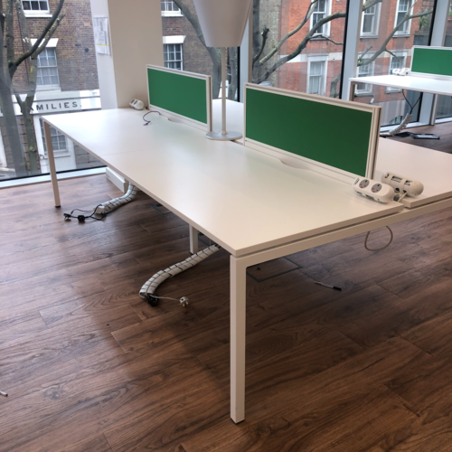 white used office bench desks with green panels