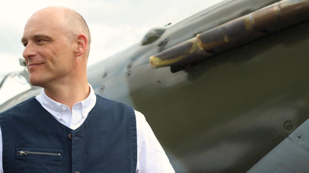 BBMF RAF Pilot Justin Helliwell stands by a Spitfire wearing Realm & Empire