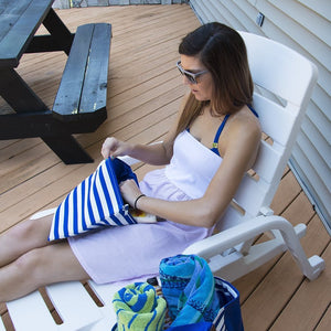 Model sitting on a pool lounge chair reaching inside her family beach pouch
