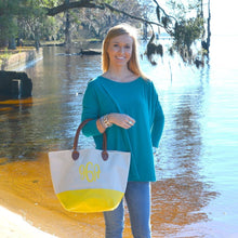 Model holding a yellow daycation tote
