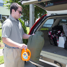 Load image into Gallery viewer, Young man loading laundry bag in the trunk of his car