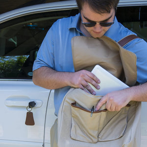 Young man inserting documents into his canvas messenger bag
