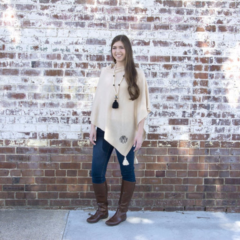 Model wearing a taupe tassel poncho