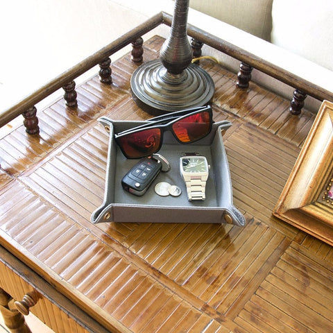 Valet tray placed on a console table carrying car keys and other men items