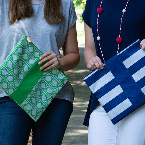 two models holding a green bamboo and blue stripe zipper pouch