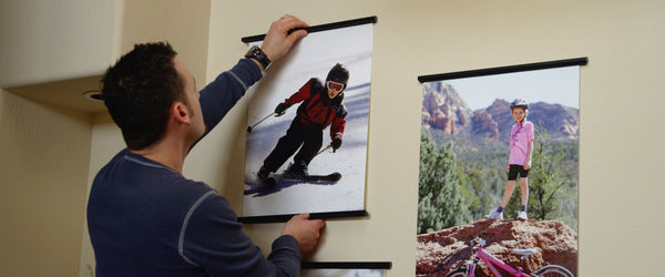 father hanging a poster of daughter skiing on a wall using a posterhanger