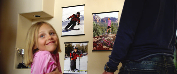child is happy to see posters of her skiing and mountain biking displayed on a wall with poster hangers