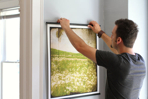 man installing Ingrid Blixt artwork on living room wall with a black posterhanger
