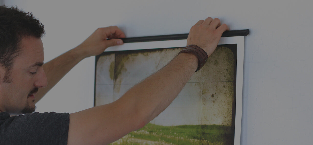 man hanging ingrid blixt artwork on wall with a poster hanger by jorgen moller