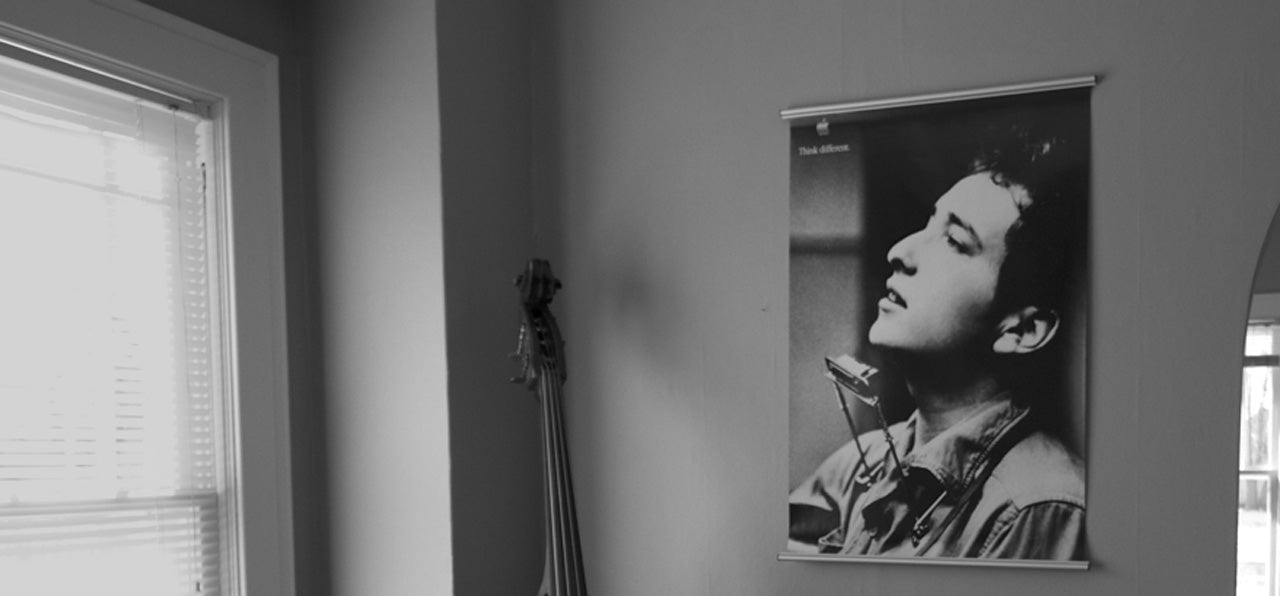 poster of bob dylan is hanging on a wall with a poster hanger by jorgen moller.  there's a stand up bass guitar in the room