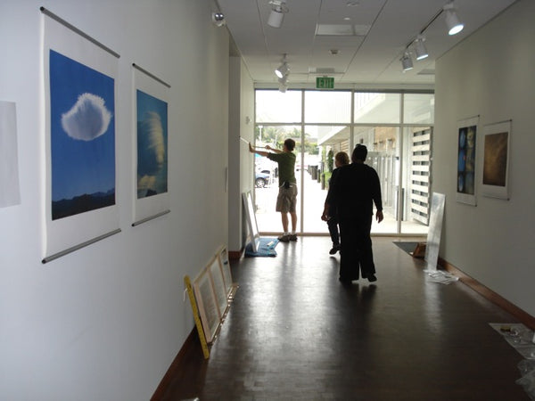 Installing Chris Garland Skyscapes exhibit with posterhanger at Annenberg Community Beach House