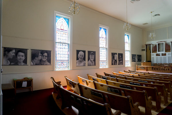 John Snell photo exhibition displayed with posterhanger inside a classic New England church sanctuary