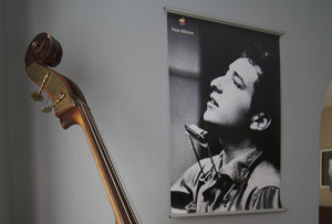 Bob Dylan Apple Think Different poster hanging on living room wall next to stand up bass guitar