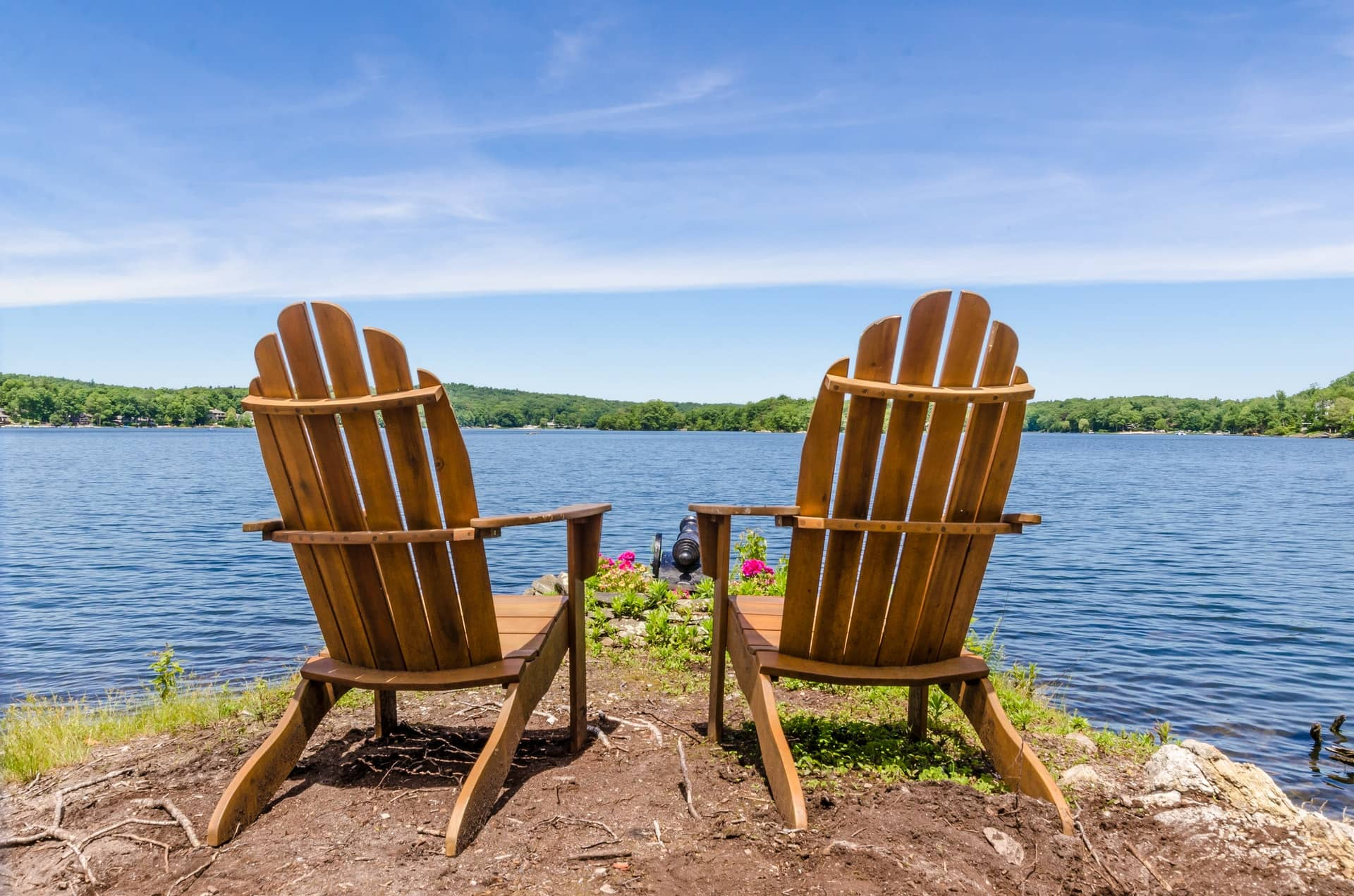 Two wooden outdoor adirondack chairs from back