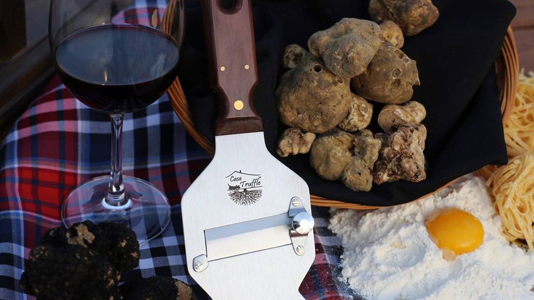 Truffle slicer beside a glass of red wine