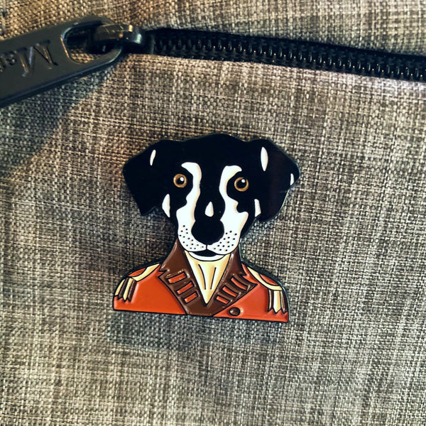 Silver-plated enamel Sir Francis Luther pin pinned to a grey backpack.