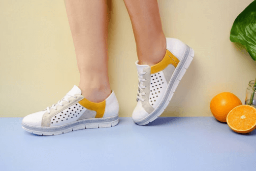 white shoes with small orange streak with oranges on the side for display