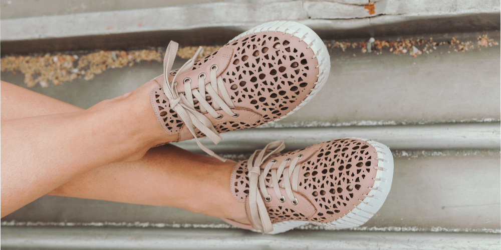 Two pink sneakers with sand underneath