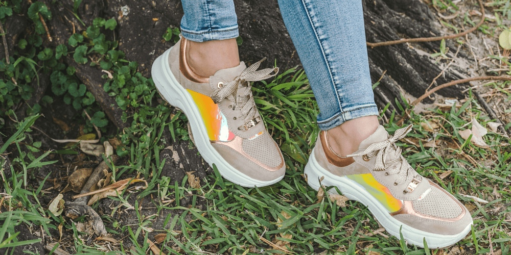 Colourful sneakers with light blue jeans dangling over a grass lawn