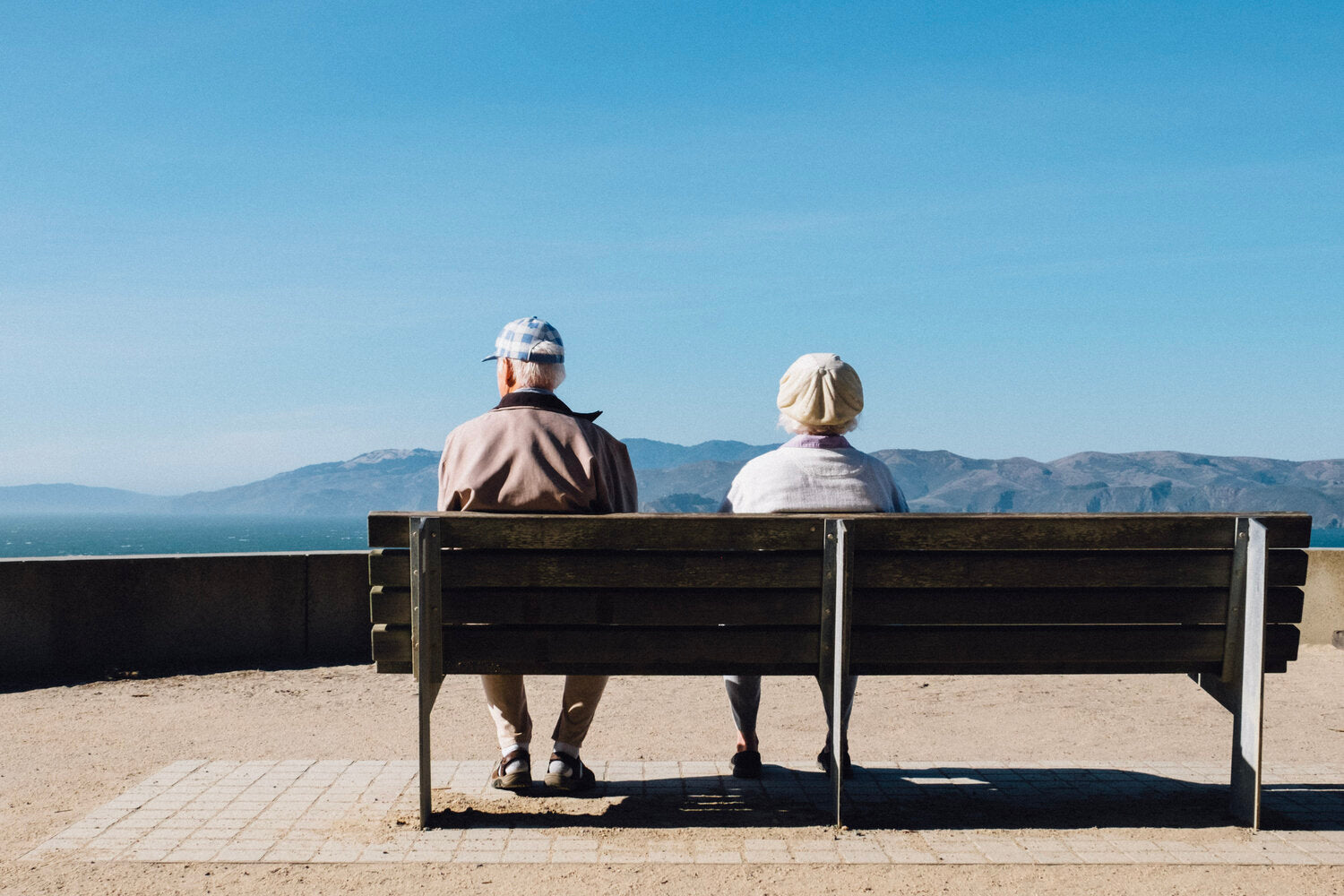 Elderly Couple With Asthma Sitting on Bench Looking Over Mountain Range