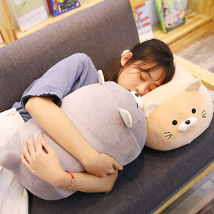 girl hugging grey cat plushie pillow and lying on khaki cat plushie pillow