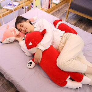 girl hugging big red fox plushie and lying on pink fox plushie