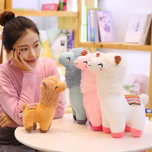 small brown alpaca llama plushie with blue, pink and white alpaca llama plushies