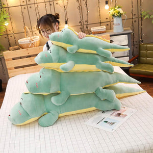 green dinosaur plushies stacked up