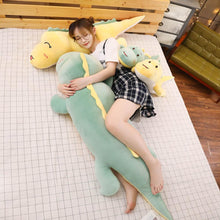 Load image into Gallery viewer, girl hugging green dinosaur plushie while lying on yellow dinosaur plushie